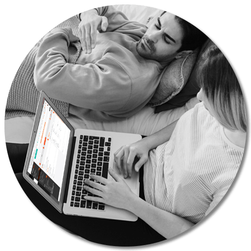 Couple installer dans leur chambre utilisant le planificateur de voyages Planning Motion sur un portable
